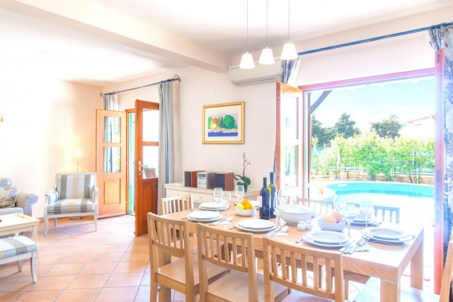 Dining room in Villa Cvita with opened French doors and exit to the swimming pool