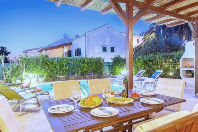 Relaxing atmosphere in the yard of the Villa Cvita with illuminated swimming pool,open fireplace and served dining table
